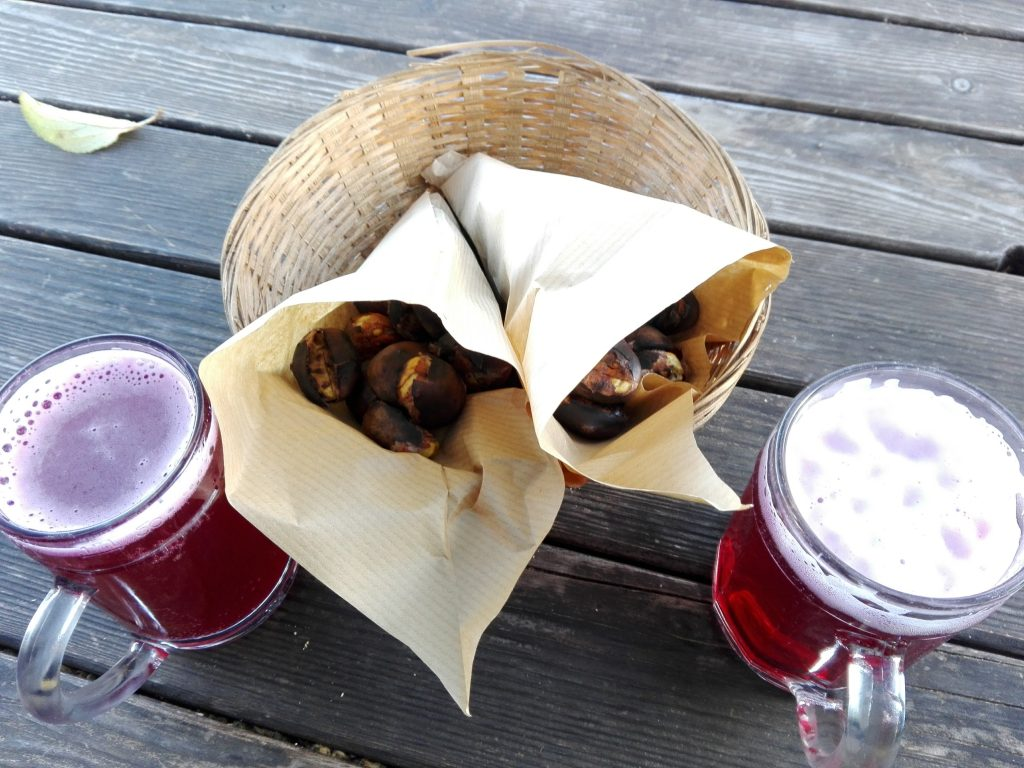 two cups of sturm and a bag of chestnuts on a table