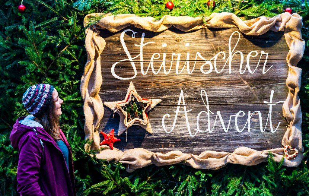 """Giulia in front of a sign saying """"Steirischer Advent"""""""